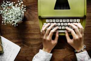 person typing on typewriter